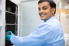 Closeup portrait, smiling young lab researcher holding tissue culture dishes  Stock Photos