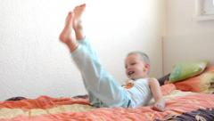 Child(little boy) jumps on the bed - kid jumping Stock Footage
