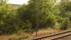 Moving train on the tracks - city (buildings) and trees - railway yard - window Stock Footage