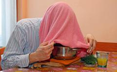 man with towel breathe balsam vapors to treat colds and the flu - stock photo
