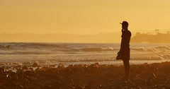 Young man standing on ocean beach looking waves sunset. Malibu California 4K UHD Stock Footage