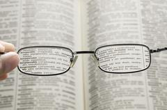 seeing dictionary through glasses - stock photo
