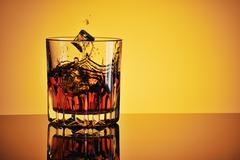 Glass of whisky with ice and splash - stock photo
