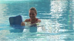 Girl with kickboard in the pool, doing water fitness Stock Footage