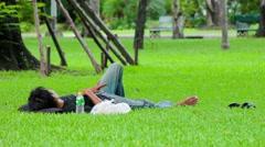 Thai man takes a nap in grass, Lumphini park, Bangkok Stock Footage