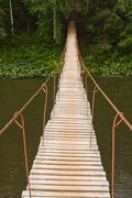 suspended bridge above the river - stock photo