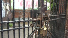 Locked Gate to Scruffy Yard with brick walls and graffiti tags Stock Footage