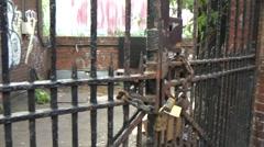 Locked Gate to Scruffy Yard with brick walls and graffiti tags - stock footage