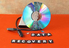 Broken dvd disc with data recovery text - stock photo