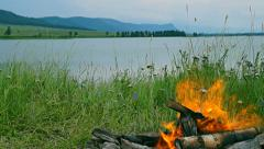 Bonfire on a background of lake and mountains Sayan. Primordial nature Stock Footage