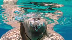 Underwater swimming, man breathing out air bubbles underwater Stock Footage