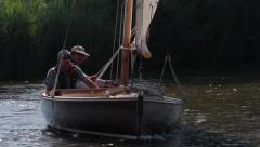 Two men sailing a wooden dingy on the Norfolk Broads - stock footage