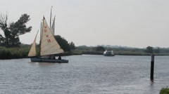 Sail dinghy and yacht weaving down the River Bure in Norfolk Stock Footage