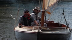 Two men sailing in wooden dingy on the Norfolk Broads Stock Footage