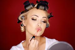 Woman applying makeup with her hair in curlers Stock Photos