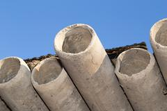 asbestos cement pipes against the blue sky - stock photo