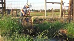 COWBOY RANCHER irrigating pasture, Stock Footage