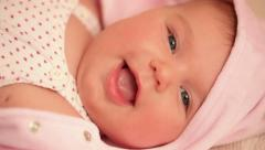 Сute two month old baby lying on back and smiling. Close-up. Stock Footage