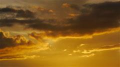Clouds darkening on orange sunset sky background Stock Footage
