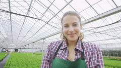 Female worker in the agricultural industry holding a young seedling in her hands - stock footage