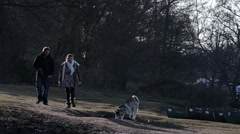 Couple walking their dogs at Salhouse Broad Stock Footage