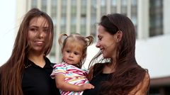 Young beautiful girl with a baby in her arms.Sisters, girlfriend and daughter. - stock footage