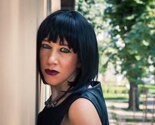 Pretty goth girl posing in a city park Stock Photos