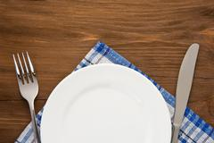 white plate, knife and fork on wood - stock photo