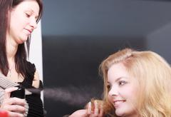 girl with blond wavy hair by hairdresser. hairstylist with hairspray and fema - stock photo
