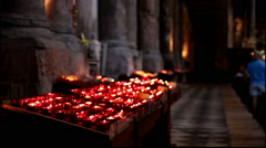 Red votive candles burn during a catholic mass - with sound Stock Footage