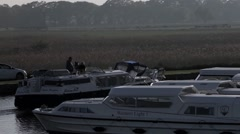 Motor cruiser pulls into moorings on Norfolk Borads Stock Footage