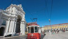 Iconic 100 year old tram passes by the augusta street arch in lisbon Stock Footage