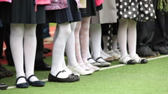 Feet of schoolgirls in white pantyhose. Children standing in line Stock Footage