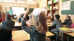 First grader girl pulling her hand in class at school. September 1. Rear view - stock footage