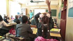 First grader girl waving her hand in class at lesson in school - stock footage
