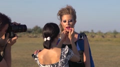 Makeup - applying lipstick to model young sexy girl before photo shoot - stock footage