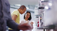 Couple shopping in a store selling kitchen appliances, white goods & electronics - stock footage