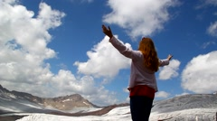 A young girl stands on top of the hands up over the mountains and glaciers Stock Footage