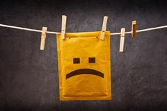 Sad face emoticon on mail envelope Stock Photos