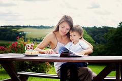 Mother and son, reading a book outdoor, summer day Stock Photos