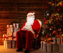 santa claus sitting on rocking chair in wooden home interior with gift boxes  - stock photo