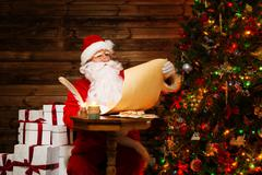 Santa claus in wooden home interior reading wish list scroll Kuvituskuvat