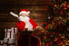 santa claus  in wooden home interior with letters and quill pen in hands - stock photo