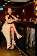 Beautiful blond woman in evening dress sitting near bar counter with cocktail Kuvituskuvat