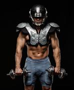 american football player with dumbbells wearing helmet and protective armour - stock photo