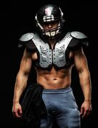 American football player wearing helmet and protective armour Stock Photos