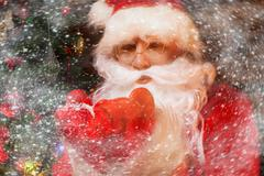 santa claus in wooden home interior blowing snow from his hands - stock photo