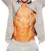 handsome man in grey hoodie showing his abdominal muscles - stock photo