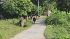 Peasant woman with sickle on the road, Asia Stock Footage