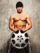 Handsome sporty man with muscular body holding alloy wheel Stock Photos